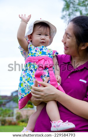 Happy asian woman and cute little girl relaxing at home back yard and bright sky background, mother carrying  her daughter