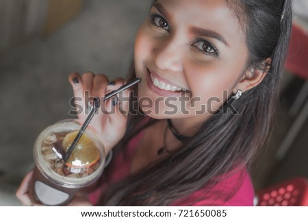 Shutterstock Happy asian woman drinking ice tea with lemon in coffee shop, Selective focus on face