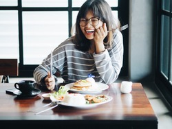 Happy Asian woman enjoy with big lunch in coffee shop.