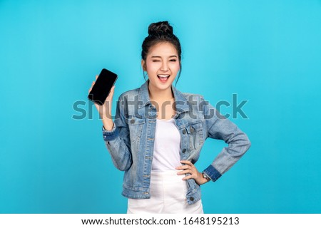 Happy asian woman feeling happiness, blinks eyes and standing hold smartphone on blue background. Cute asia girl smiling wearing casual jeans shirt and connect internet shopping online and present Foto stock ©