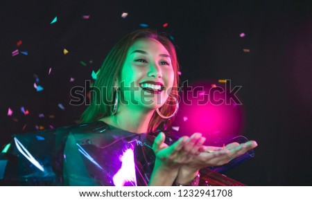 Happy Asian woman have wish on her hand of celebrate the Christmas season and New Year with colorful confetti in night background,Bright close up picture of magic twinkles on female hands at party,