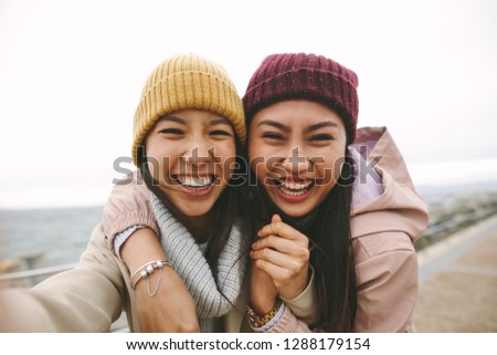 Happy asian woman in winter wear standing near the sea on a cold morning. Smiling women standing outdoors holding each other and having fun on a winter morning. Stock fotó ©