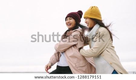 Happy asian woman in winter wear standing outdoors on a cold winter morning. Cheerful women standing outdoors holding each other and having fun on a winter morning. Stock fotó ©