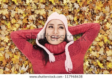 Happy Asian woman laying on Autumn leaves in the park