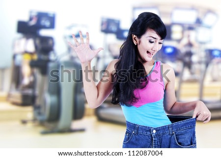 Happy asian woman posing in gym with her old big pants