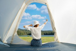 Happy Asian woman sitting with stretching her arms in a camping tent while admiring beautiful calm lake with dense woods and clear blue sky with white clouds in front of her during a warm sunny day.