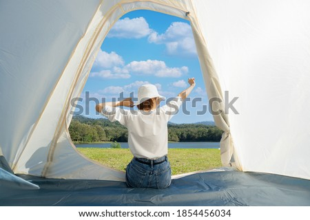 Happy Asian woman sitting with stretching her arms in a camping tent while admiring beautiful calm lake with dense woods and clear blue sky with white clouds in front of her during a warm sunny day. 商業照片 ©