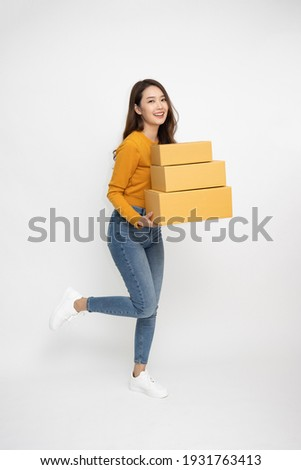 Happy Asian woman smiling and holding package parcel box isolated on white background, Delivery courier and shipping service concept, Full Length people composition