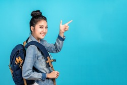 Happy asian woman travel backpacker standing pointing hands to copyspace on blue background. Cute asia girl smiling wearing casual jeans shirt and finger pointing to aside for present promotions.