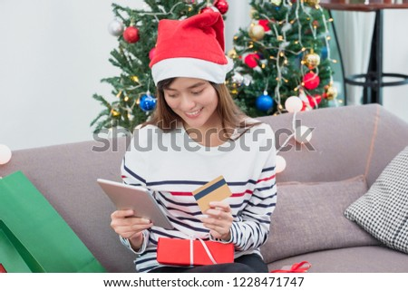 Happy Asian woman use credit card buy Christmas gift with mobile apps on tablet at home in party,Holiday online shopping, Mobile banking payment