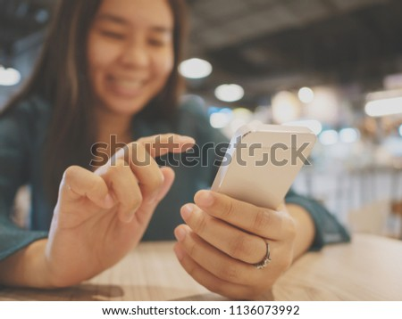Happy asian woman using smartphone in restaurant, She is typing messages with her friends through the chat application on mobile phone