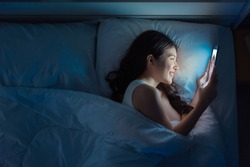 Happy asian woman video calling a boyfriend in a tablet on the bed in the night