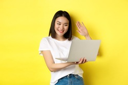 Happy asian woman video chat on laptop, waiving hand at computer camera and saying hello, standing over yellow background