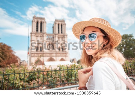 Happy asian woman visiting famous Notre Dame Cathedral after the Fire. Europe travel and sightseeing tours concept