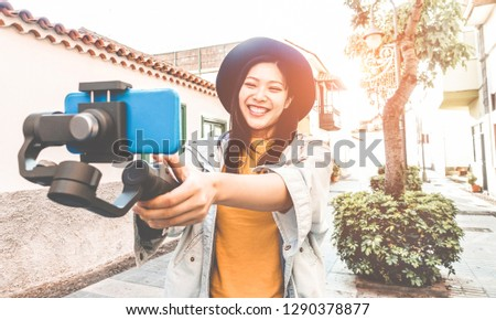Happy asian woman vlogging with gimbal tripod and smartphone - Influencer chinese girl having fun with new trend technology - Millennial generation activity job, youth and tech concept - Focus on face