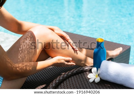 Happy Asian woman wearing swimsuit, hat lying on sunbed applying sun cream and relaxing at the poolside. Sunburn protection. Summer holidays and vacation concept. Stock foto ©
