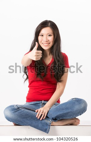 Happy Asian woman with thumb up in approval. Isolated on white background.