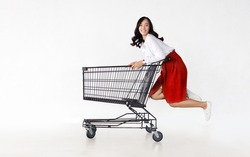 happy asian woman with trolley shopping cart in sideview on white isolated background