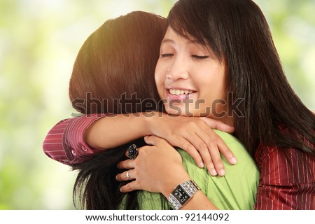 happy asian women hugging each other and smiling