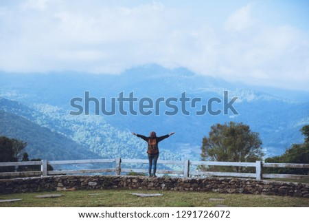 Happy Asian women Travel relax Standing at the view point Look at the watching the nature View of mountains the mist beautiful at sheep farm Doi Inthanon. #1291726072