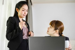 Happy Asian workingwomen working together at computer laptop. The successful businesswomen learning about e-commerce/e business as online technology is changing. Teamwork& collaboration concept.
