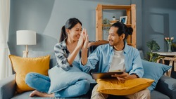 Happy asian young attractive couple man and woman sit on couch use tablet shopping online furniture decorate home in the living room at new house. Young married moving home shopper online concept.