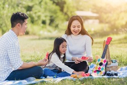 Happy Asian young family father, mother and child little girl having fun and enjoying outdoor sitting on picnic blanket eating watermelon fruit snack lunch in park sunny time, summer leisure concept