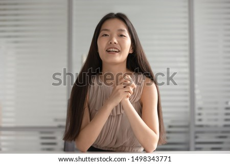 Happy asian young girl presenting herself at distant job interview. Smiling korean professional language teacher giving lesson to client, communicating via video call, recording educational lecture.