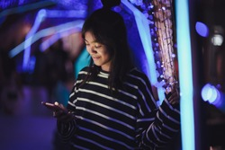 Happy asian young girl using a mobile phone in downtown, Bokeh city light in background