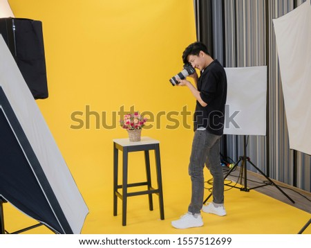 Happy Asian Young male professional photographer shooting photo with a digital camera in a professionally equipped studio.