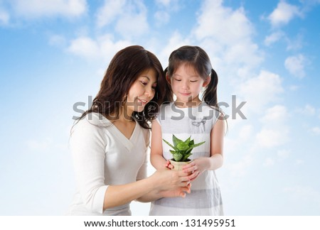 Happy Asian young mother with daughter taking care plant in summer day, blue sky as background.