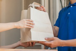 Happy asian young woman protect  pandemic of covid-19 and received paper bag from delivery man, messenger in blue uniform while lockdown, quarantine at front door home, apartment.