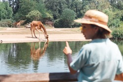 Happy asian zoology student girl looking at giraffe drinking from lake