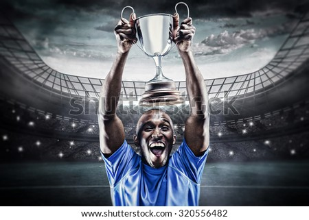 Happy athlete cheering while holding trophy against large football stadium under blue sky