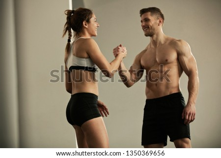 Happy athletes congratulating and supporting each other after sports training in a health club.