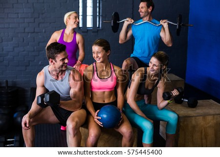 Happy athletes with exercise equipment in fitness studio