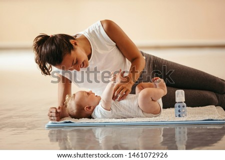 Happy athletic mother playing with her baby boy who is lying on exercise mat in health club.