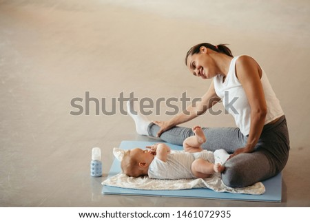 Happy athletic mother stretching on the floor while being with her baby in a health club.