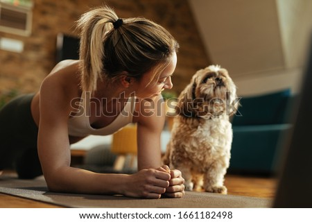 Happy athletic woman doing plank exercise while her dog is sitting next to her.