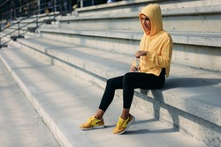 Happy athletic woman in yellow hoodie and black leggings holding bottle with water while sitting on steps. Concept of refreshing and recreation.