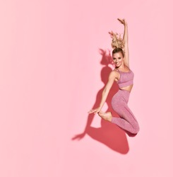 Happy athletic woman jumping in silhouette. Photo of sporty woman in fashionable pink sportswear on pink background. Sport and healthy lifestyle. Dynamic movement.