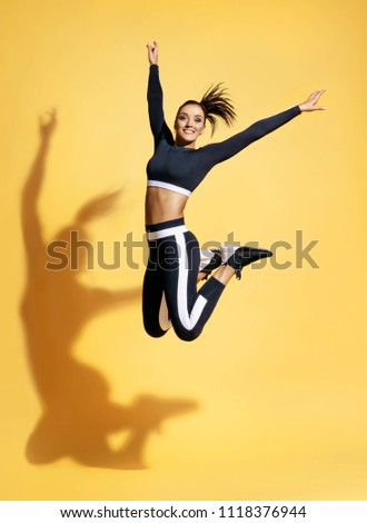 Happy athletic woman jumping up in silhouette. Photo of sporty woman in fashionable black sportswear on yellow background. Dynamic movement. Sport and healthy lifestyle