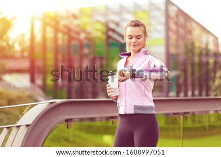 Happy athletic young woman resting after jogging – Modern female fitness runner listening music on earphones while checking heart rate looking at smartwatch – Sport lifestyle