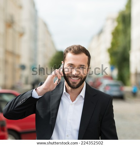 Happy attractive businessman on his mobile phone chatting as he walks along an urban street looking at the camera with a beaming smile