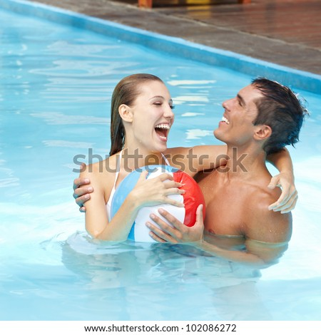 Happy attractive couple having fun in pool with beach ball