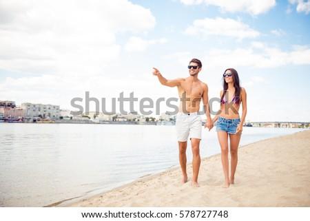Happy attractive couple walking on beautiful sunny beach. #578727748