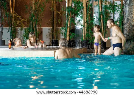 Happy attractive family relaxing by the pool