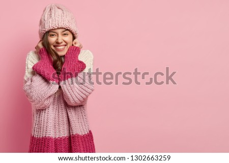 965e107f0d78d2 Happy attractive female youngster keeps hand near ears, dressed in warm  knitted sweater and headgear