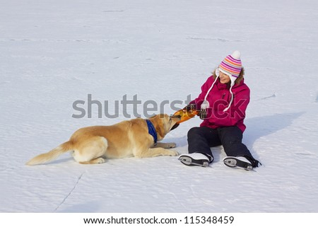 Happy attractive girl with ice skates playing with her dog on frozen lake