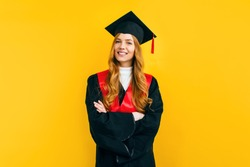 Happy attractive graduate in a master's dress, on a yellow background. Concept of the graduation ceremony